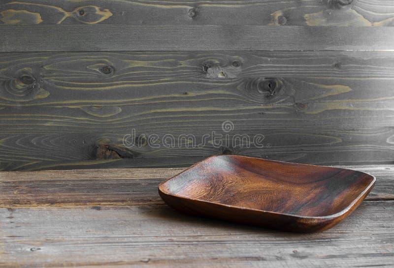 Brown obciosuje płaskiego drewnianego pustego talerza na texutred naturalnym stole robić od szalunku normalny k?t Horyzontalny z  fotografia stock