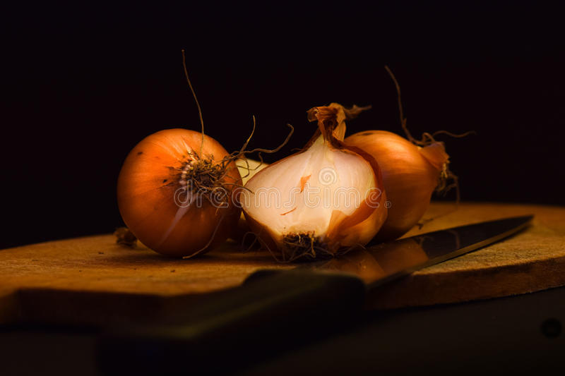 Download Brown Onions On A Wooden Cutting Board Stock Photo - Image: 83708519