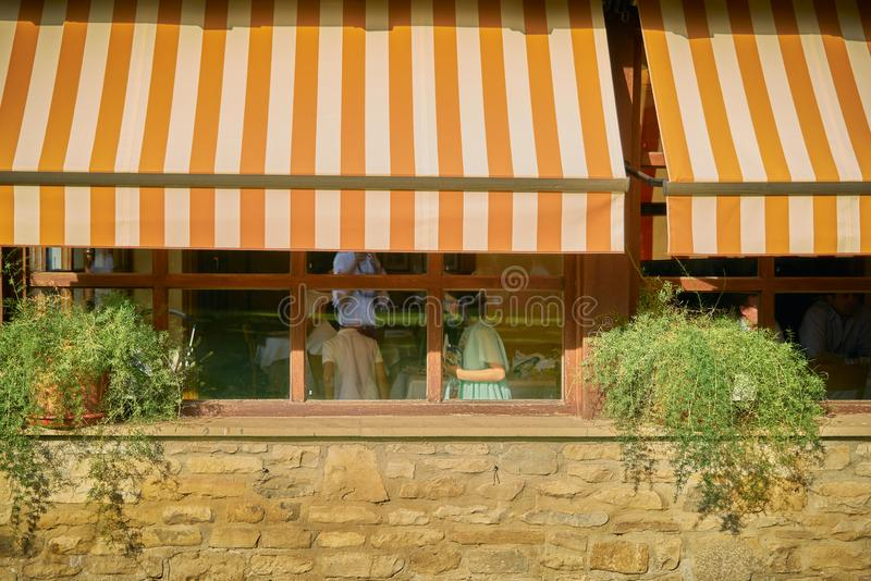 brown orange and white awning covering a window in a restaurant while unidentified people are inside stock image