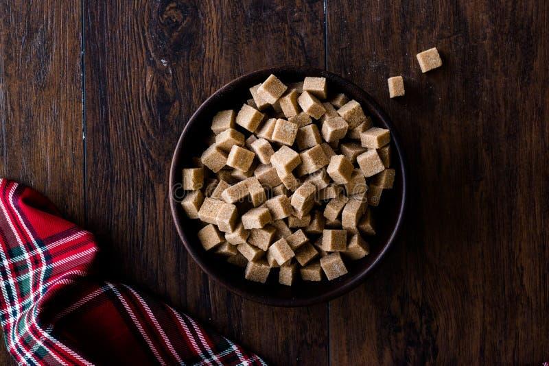 Brown orgânico cru Sugar Cubes na bacia de madeira pronto para comer foto de stock