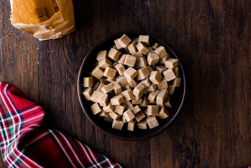 Brown orgânico cru Sugar Cubes na bacia de madeira pronto para comer imagens de stock