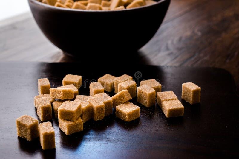 Brown orgânico cru Sugar Cubes na bacia de madeira pronto para comer imagem de stock
