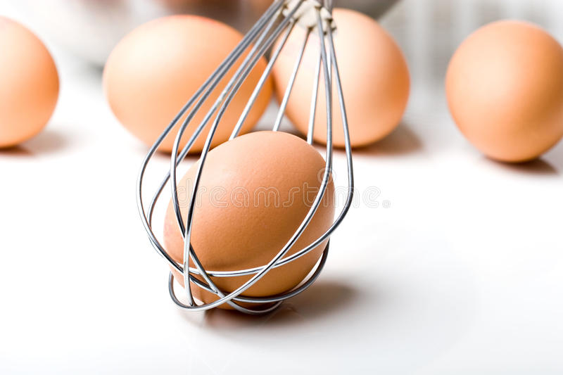 Brown organic eggs with the whisk royalty free stock images