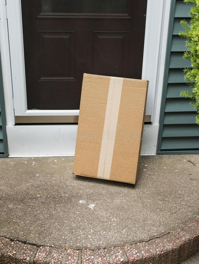 A brown package is left vulnerable at front door royalty free stock image
