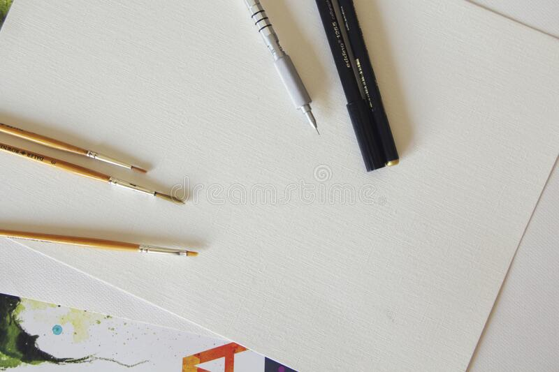 Brown Paintbrush Beside Black and Silver Ballpen on White Printing Paper royalty free stock photo