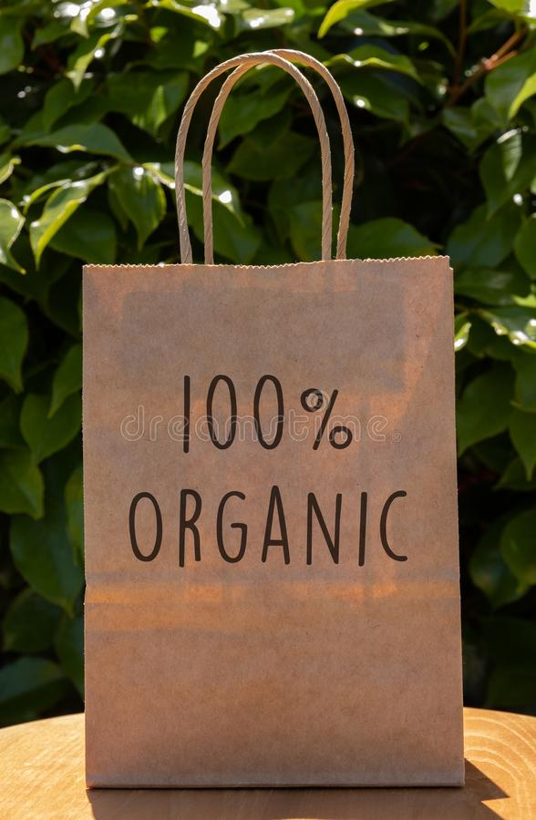 Brown paper bag with `100% Organic` message in front of a green leafy background. Paper bag message royalty free stock images