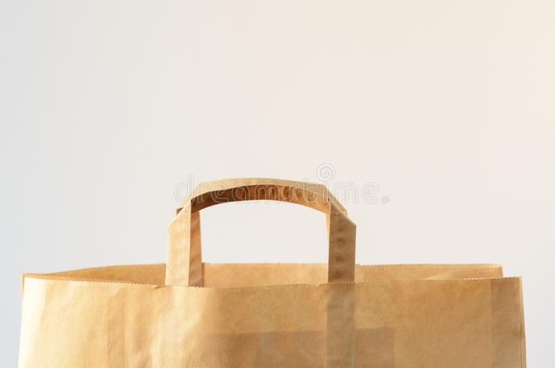 Brown paper bag on a white background. Shopping concept, eco-friendly packaging, minimal composition. Copy space. stock photos