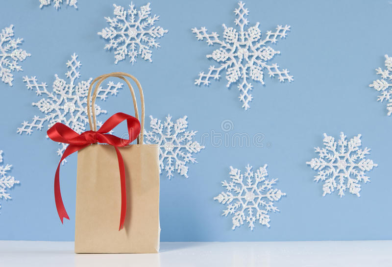 Brown paper package with red ribbon. Brown paper bag with red ribbon for christmas on blue snowflake background royalty free stock image