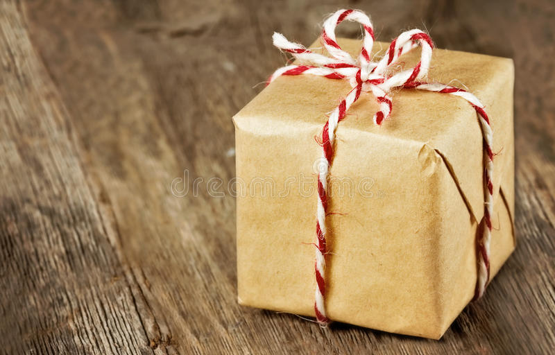 Brown paper package tied up with strings. Christmas style rustic brown paper package tied up with strings stock image