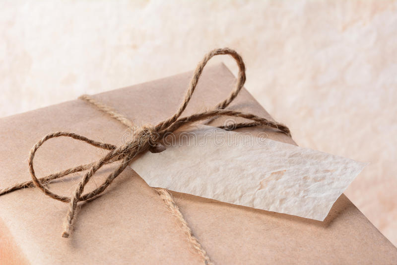 Brown Paper Wrapped Package With Gift Tag. Closeup of a brown eco friendly paper wrapped package with gift tag. Horizontal format with shallow depth of field royalty free stock images