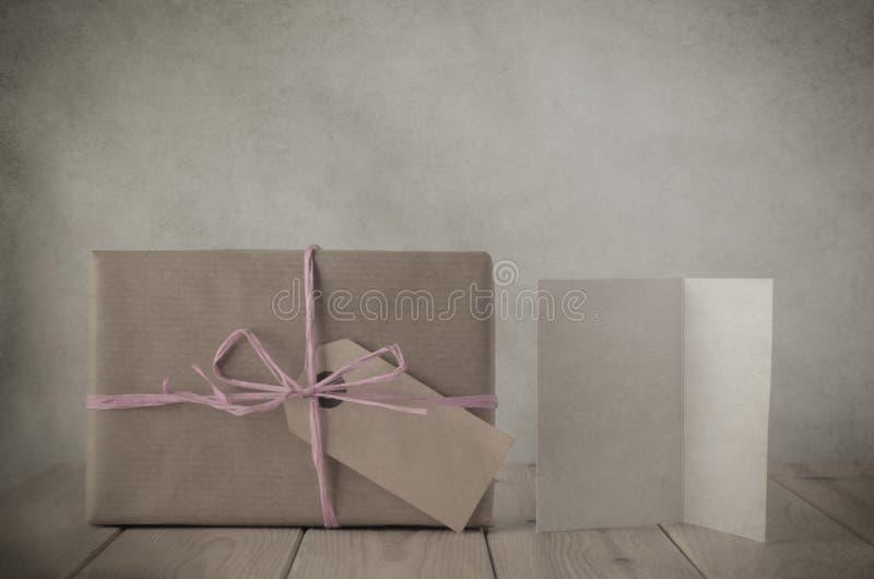 Brown-Papier-Geschenkbox mit rosa Raffiabast-und Gruß-Karte stockfotos