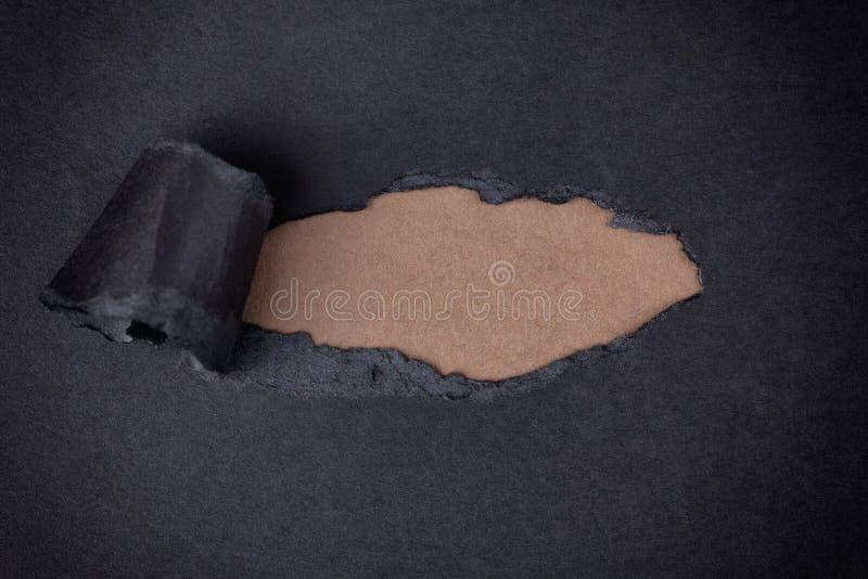 Brown-Papierhintergrund, der hinter heftigem schwarzem Papier erscheint lizenzfreies stockfoto