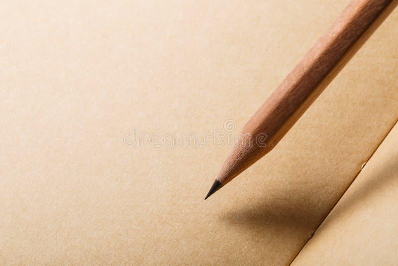 Brown-Papierhintergrund mit braunem Bleistift auf diagonalem und leerem Platz für Text lizenzfreies stockfoto