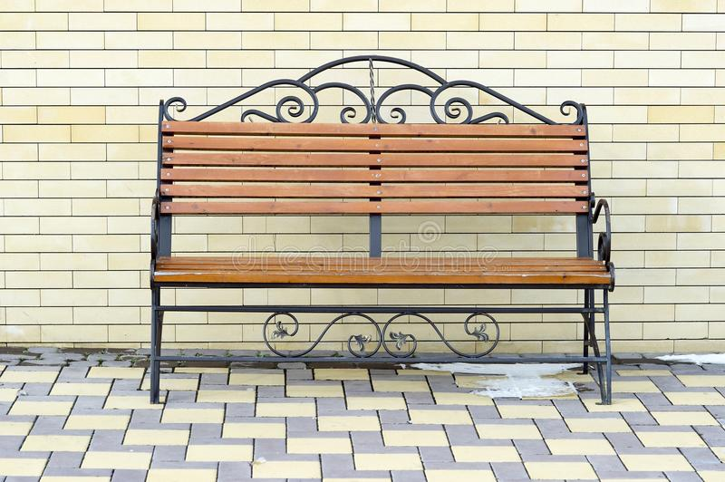 Brown Park bench against the wall of a light yellow brick. stock image