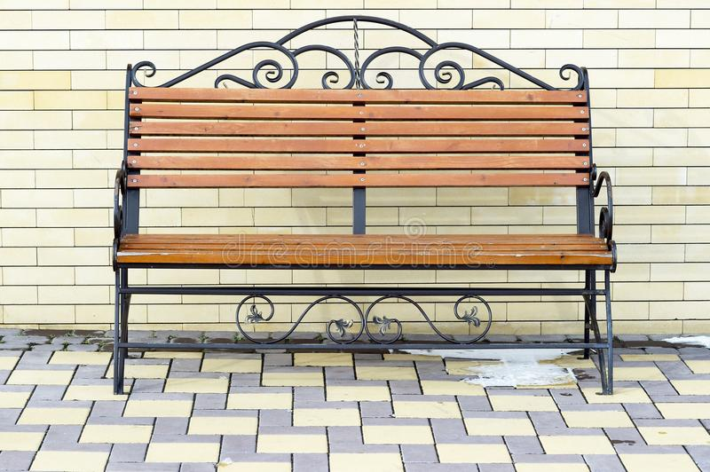 Brown Park bench against the wall of a light yellow brick. royalty free stock photo
