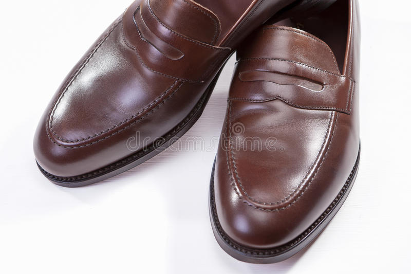 Brown Penny Loafer Shoes Against White Background. Horizontal Image Orientation. Footwear Concepts. Closeup of Pair of Stylish Brown Penny Loafer Shoes Against stock photos