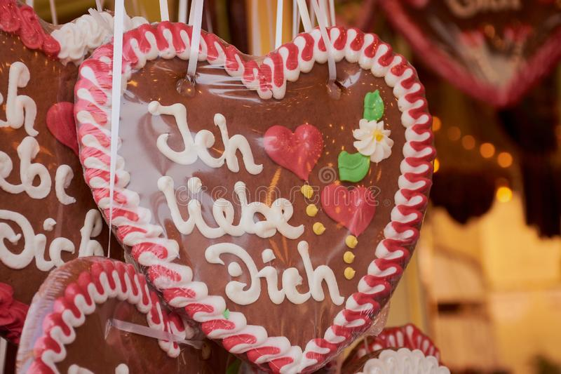 Brown gingerbread heart with the words: Ich liebe Dich. Brown pink gingerbread heart with the German words `Ich liebe Dich` which means in English: `I love you stock images