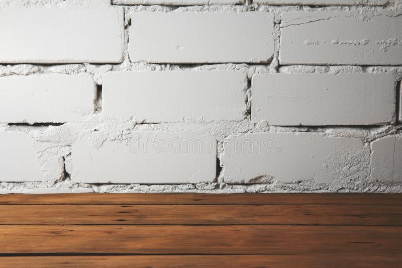 Brown plank wooden floor with white brick wall. Old plank wooden floor with white brick wall stock image