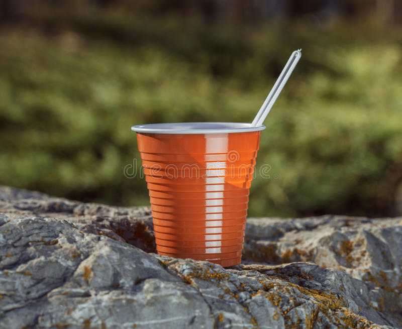 Brown plastic coffee cup with a spoon on a rock royalty free stock photos
