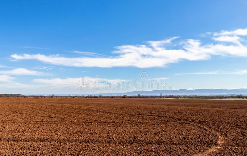 Brown plowed field prepared for sowing, beautiful blue sky and white clouds, Bulgaria. Brown plowed field prepared for sowing, beautiful blue sky and white royalty free stock images