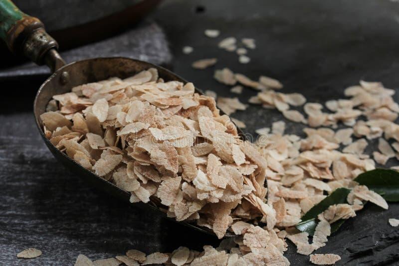 Brown Poha o Aval/ha appiattito i fiocchi del riso in un mestolo del metallo, fuoco selettivo fotografia stock libera da diritti