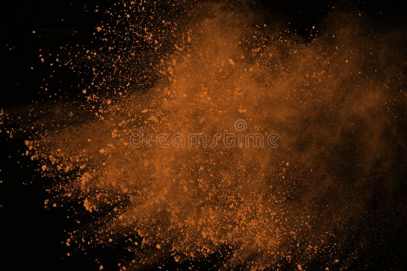 Colored powder explosion. Colore dust splatted. Brown powder explosion isolated on black background. Colored dust splatted royalty free stock photo