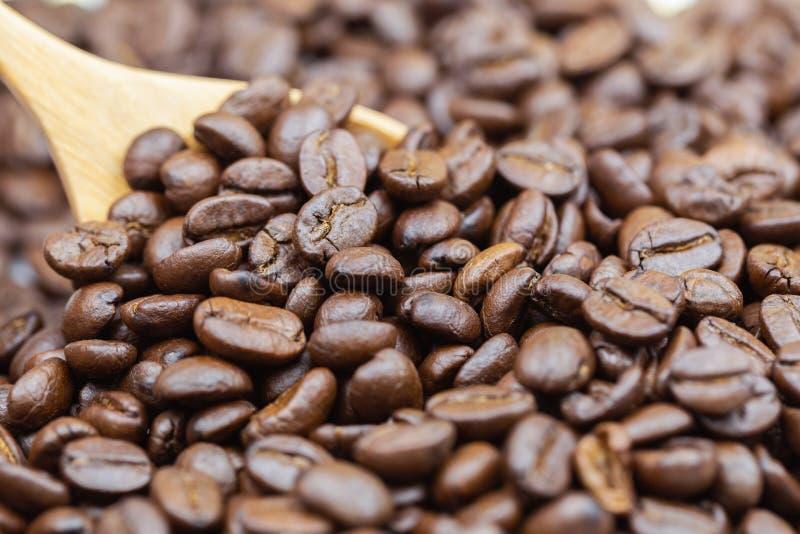 Brown a rôti la texture de grains de café avec le fond en bois de cuillère pour la conception de l'avant-projet de nourriture et  photographie stock libre de droits