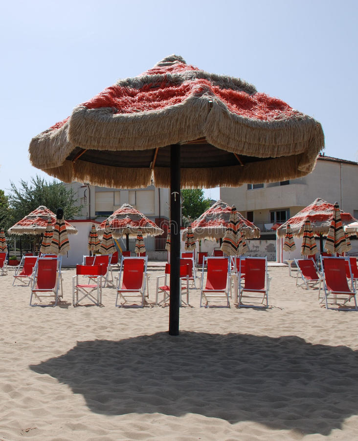 Brown and Red Fringed Beach Umbella. Red and brown beach umbrellas and deckchairs on a beach on a sunny summers day stock photo