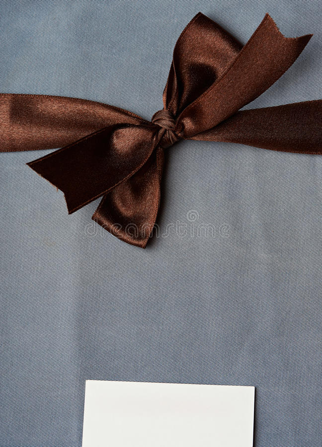 Brown ribbon on jenas background. With white tag label stock photos