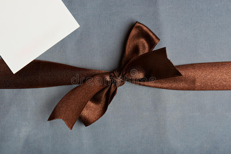 Brown ribbon on light blue background. With white tag royalty free stock photos