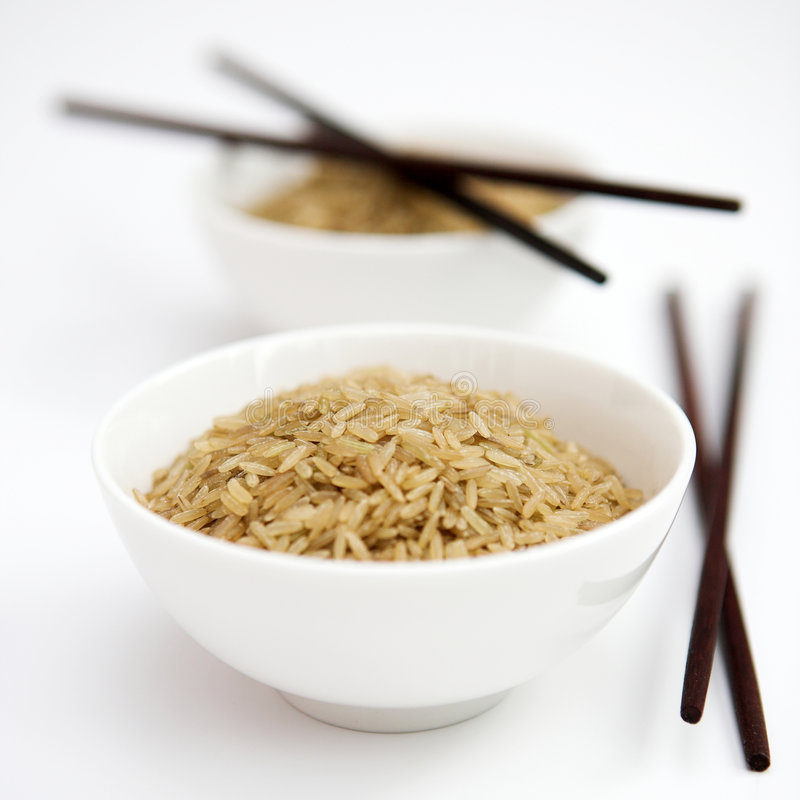 Brown rice. Bowls of uncooked brown rice & chopsticks - shallow dof royalty free stock image