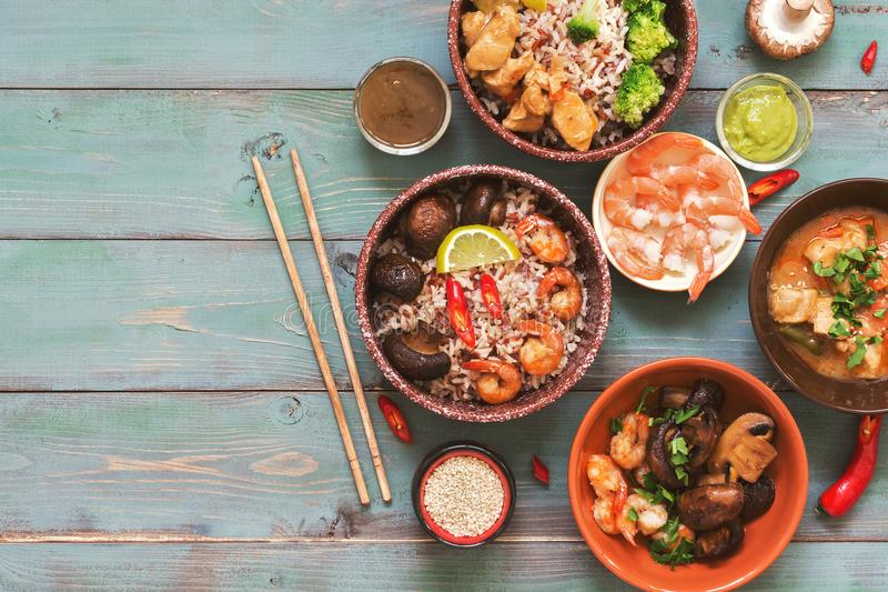 Brown rice is served with shrimps, mushrooms and chicken on a rustic background. The concept of Asian food. Top view, space for te. Xt royalty free stock photography