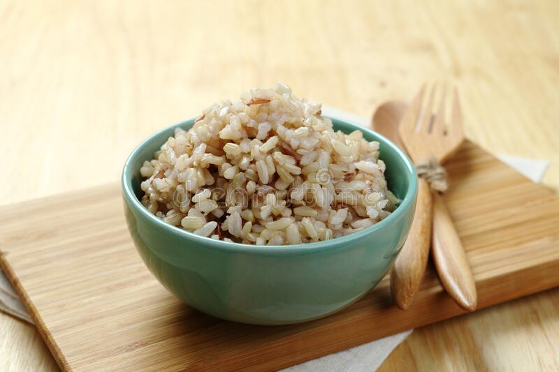 Brown Rice on Wooden Plate royalty free stock photography