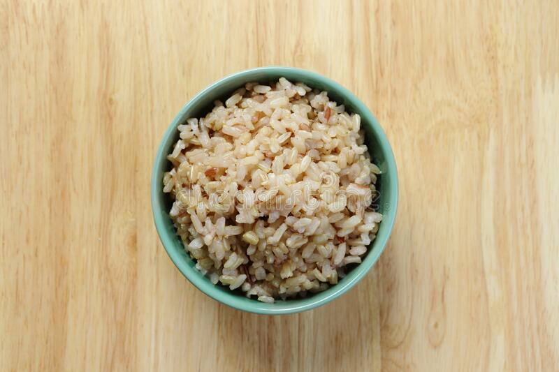 Brown Rice on Wooden Table royalty free stock images