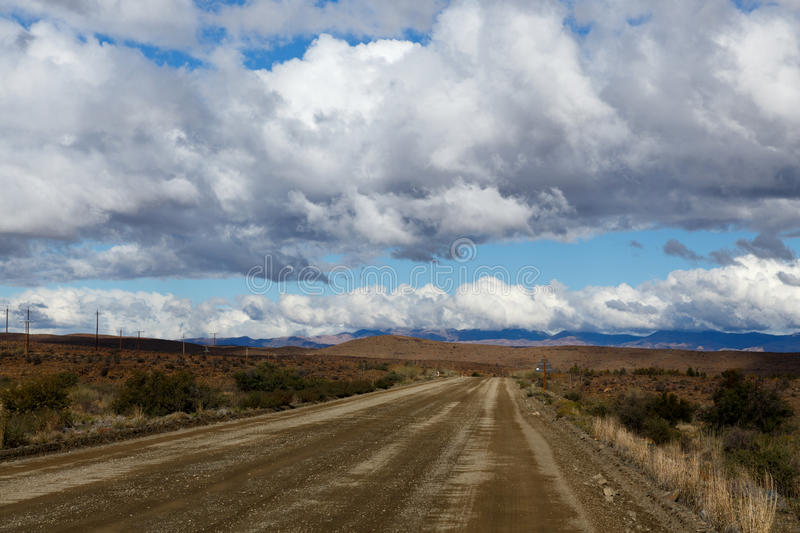 Brown Road and Cloudy Sky in Prince Albert. Prince Albert, South Africa is a small town in the Western Cape in South Africa. It is located on the southern edge royalty free stock images