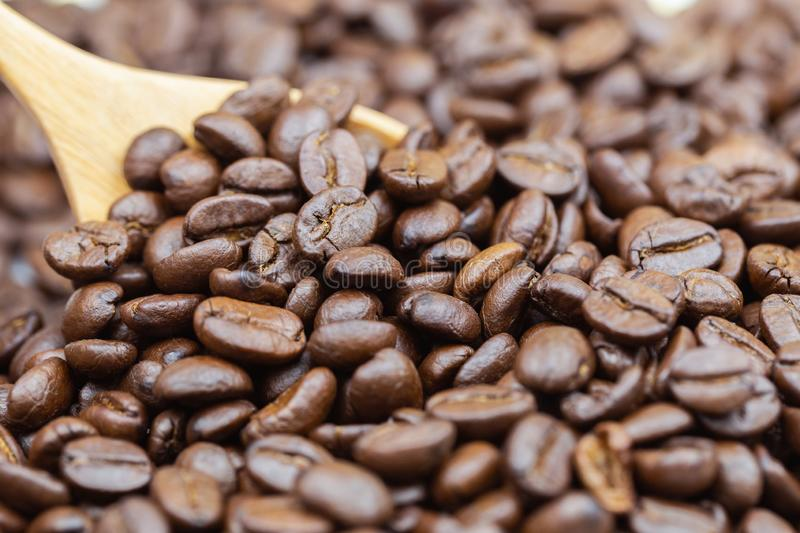 Brown roasted coffee beans texture with wooden spoon background for food and drink or agriculture concept design royalty free stock photography