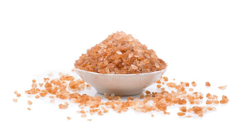 Brown rock sugar in a white bowl over white background. stock photography