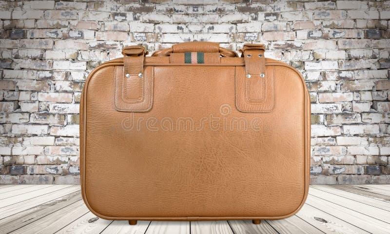 Brown rocznika rzemienna walizka na drewnianej podłoga obrazy stock