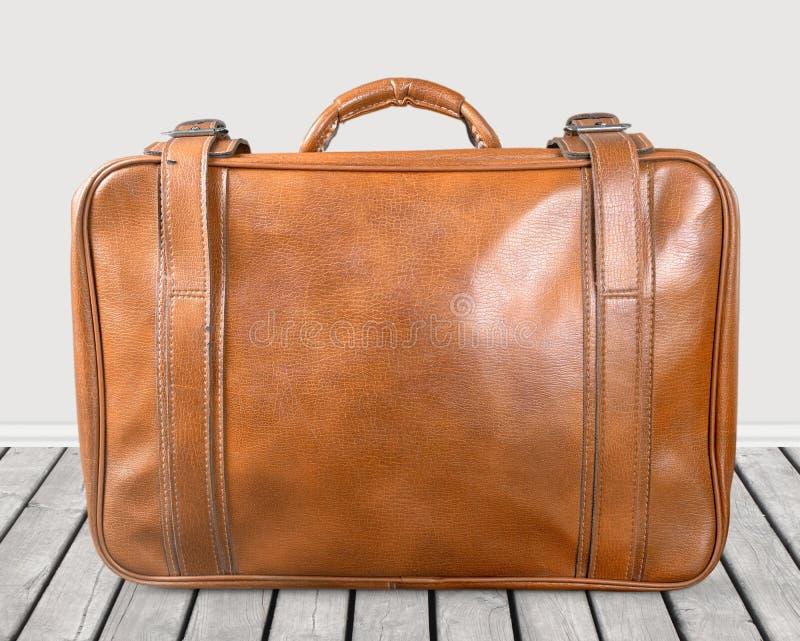 Brown rocznika rzemienna walizka na drewnianej podłoga zdjęcia royalty free