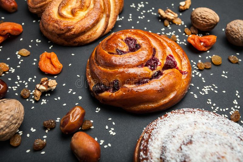 Brown rolls with cherries and sweet pastries with dry fruits and nuts on a black table.  stock photo