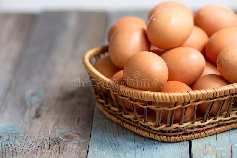 Brown rolników kurczaka bezpłatni jajka w koszu, zakończenie w górę, wieśniaka stół obrazy royalty free