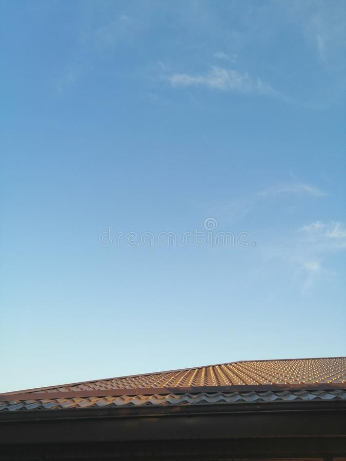 Brown roof of the house against the sky stock photos