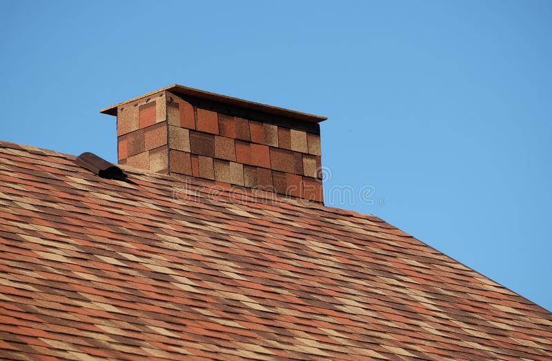 Brown roof of a house covered with soft shingles with short big smokestack close up under cloudless blue sky stock photography