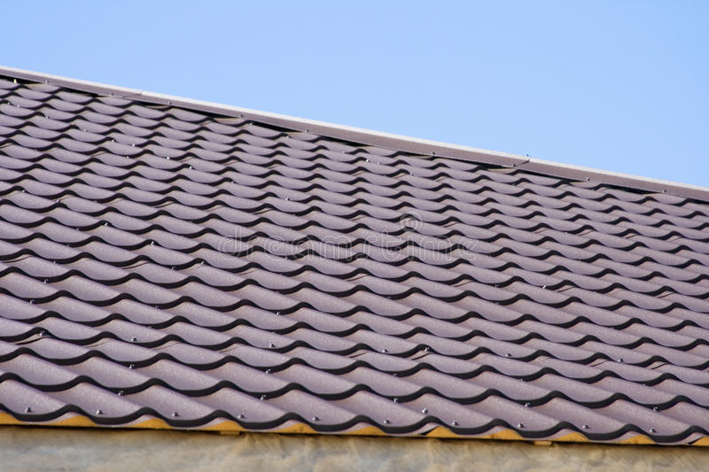 Brown roof of metal roofing on the sky background stock images
