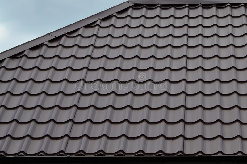 Brown roof tiles or shingles on house as background image. New overlapping brown classic style roofing material texture pattern o royalty free stock photos