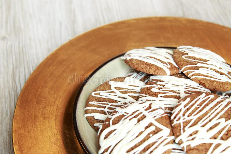 Brown Round Christmas Gingerbread cookies drizzled with White Ch. Ocolate on a plate stock photo