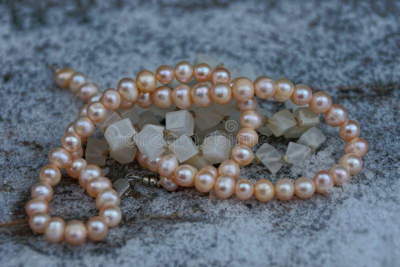 Brown-Rundenperlen und quadratische graue Perlen auf weißem Schnee lizenzfreies stockfoto