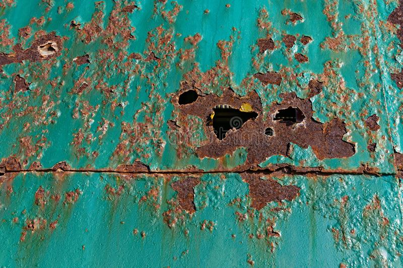 Brown rust and holes on a teal metal door royalty free stock photography
