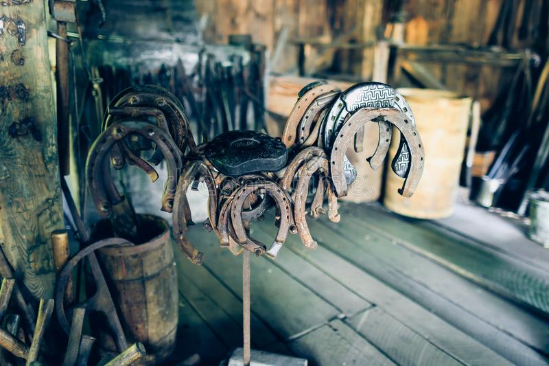 Brown rusty antique horseshoes in a barn, hooked into the nail. Fancy and old symbols of happiness. Happy rustic scenery with luck. Goods. Talisman old horse royalty free stock photography