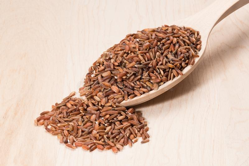 Brown ryż w drewnianej łyżce na drewnianej desce fotografia royalty free